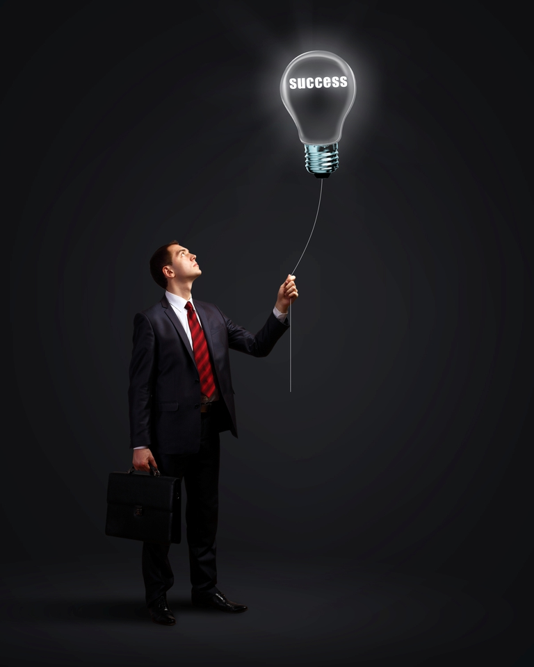 "Business man holding a light bulb that says ""Success"""
