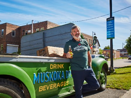 Owner Michael Billinghurst standing in front of a vintage Muskoka Springs delivery truck