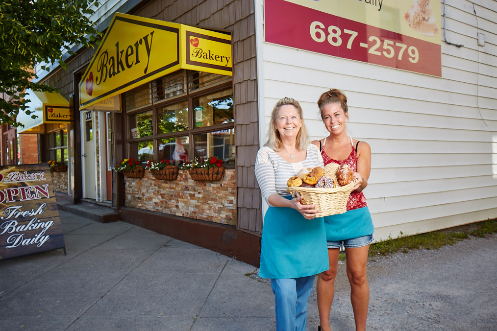 Judy and Robyn holding a basket of freshly baked bread outside their Downtown location