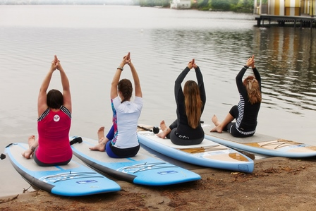 Class doing yoga on paddle boards
