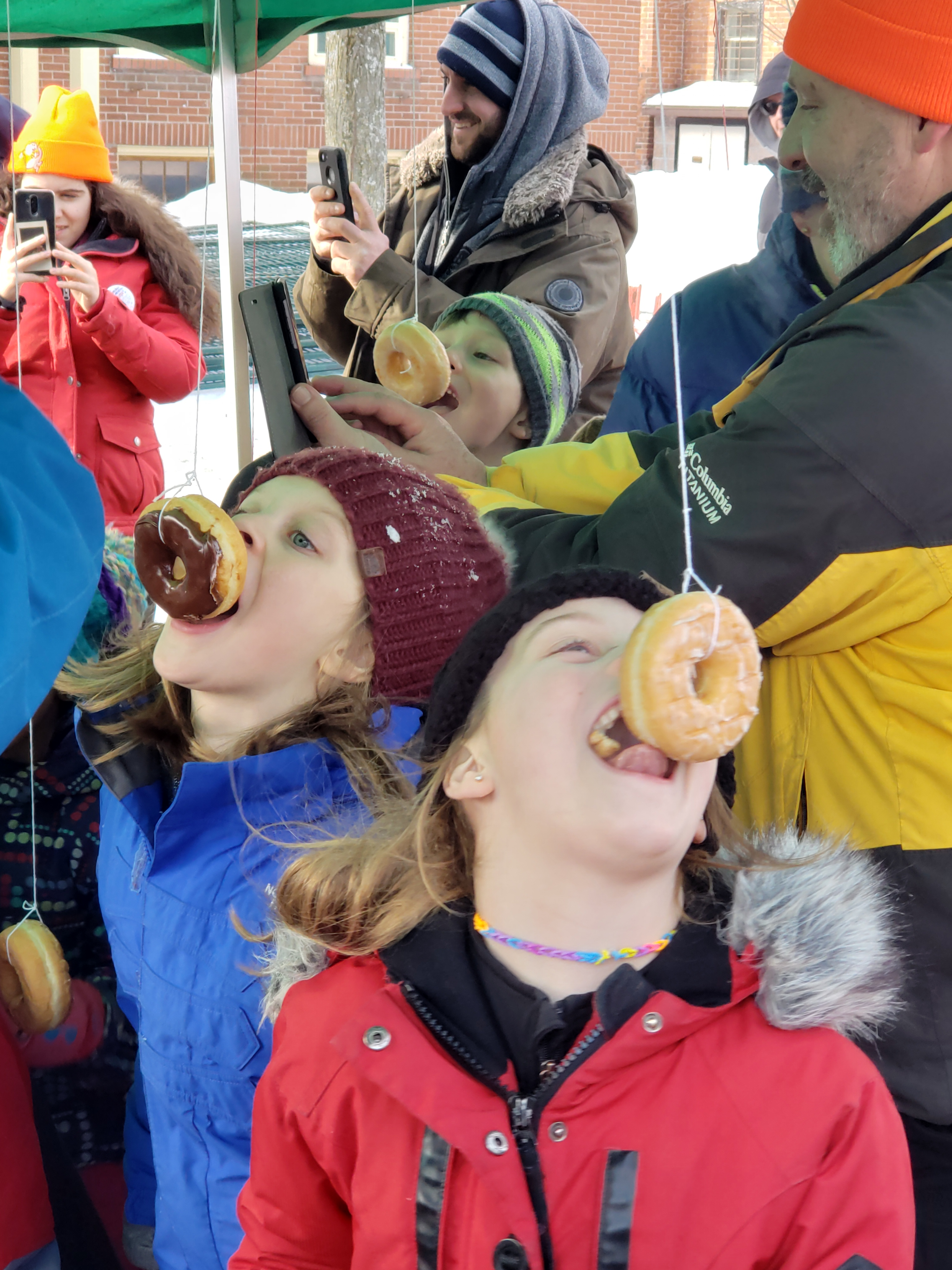 Two children at the donut eating contest at the Winter Carnival.