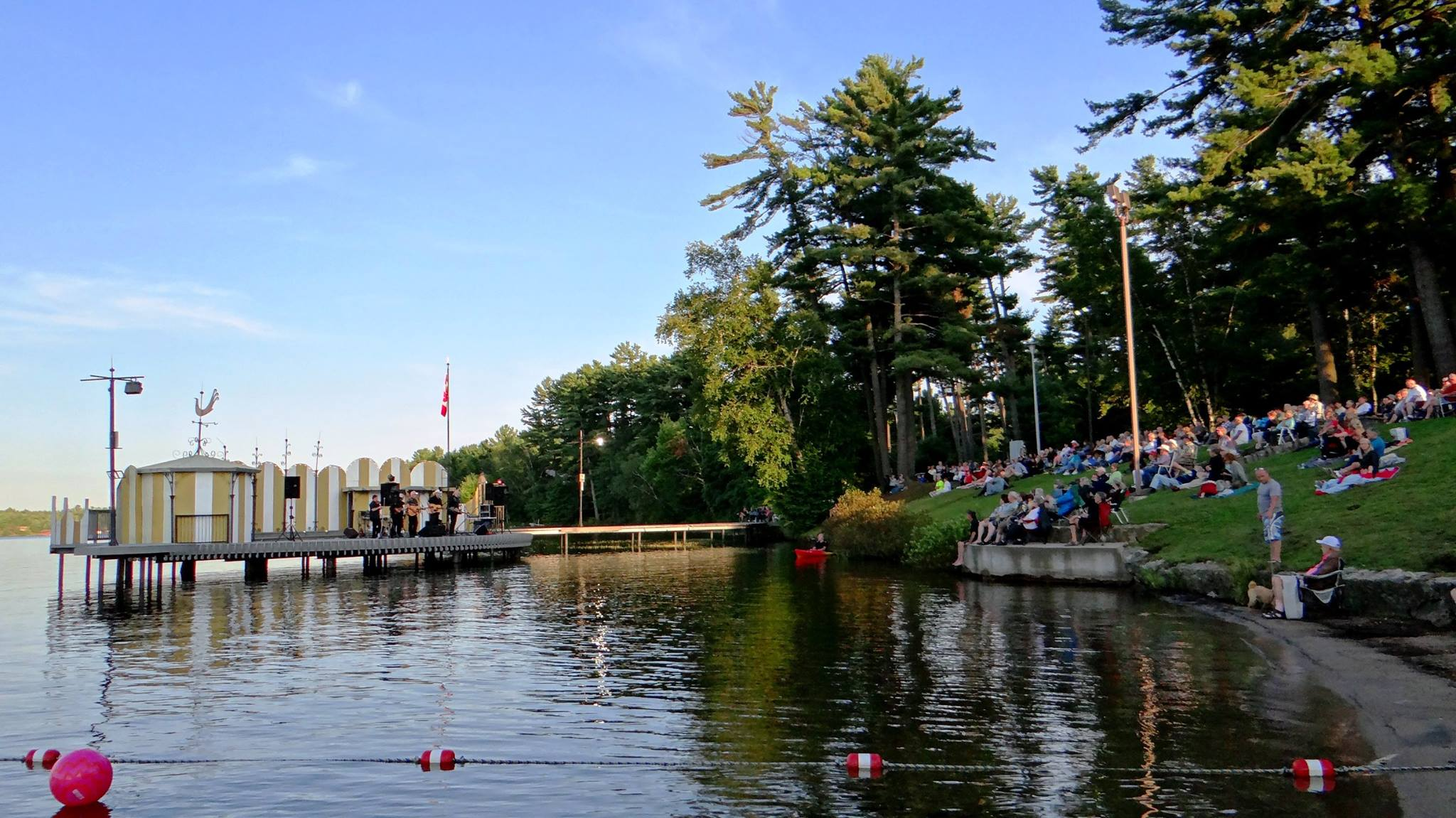 Scenic photo of a band performing on Music on the Barge and Gull Lake with fans