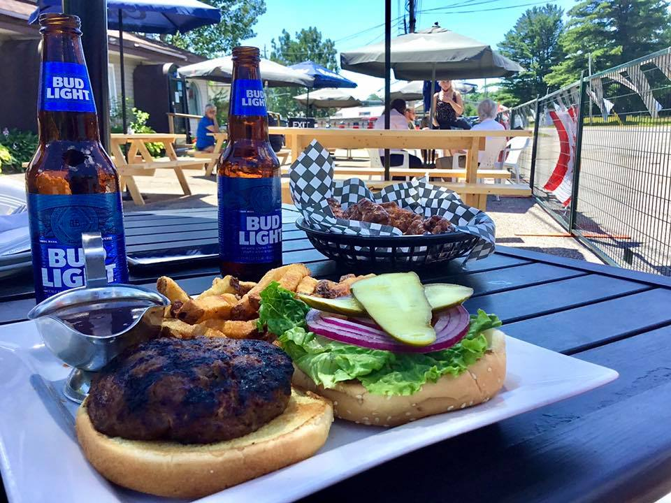 A burger and two beers on a patio