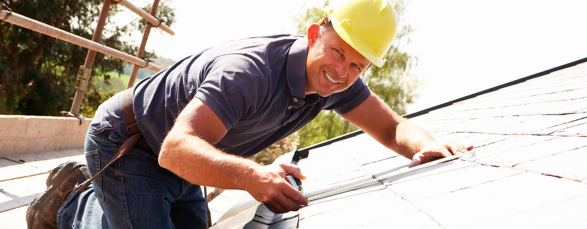 Builder on roof top with measuring tape. Building Information Banner Image
