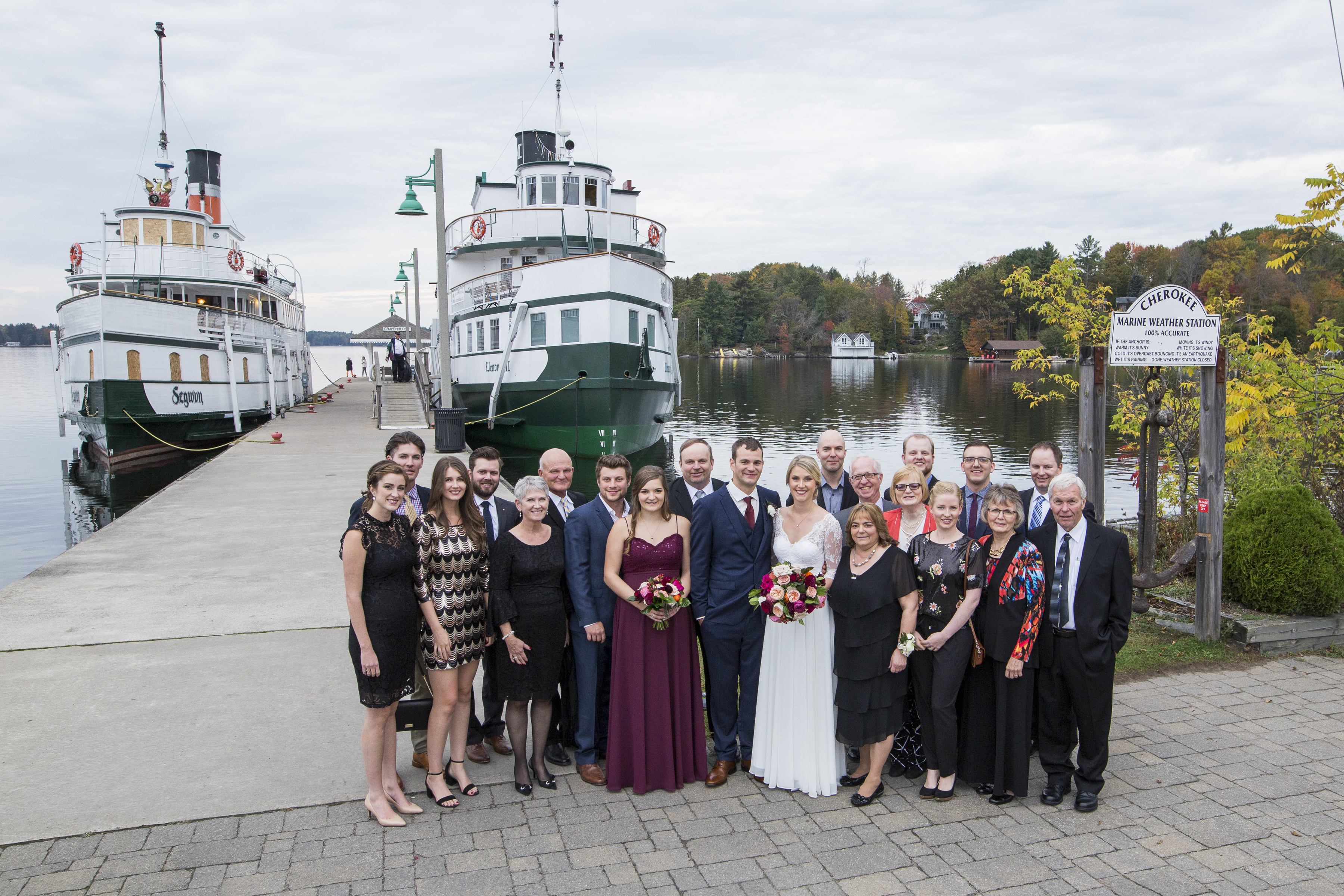 Photo of a wedding party standing at the Muskoka Wharf with the Steamships in the background