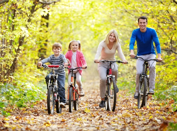 family biking through the forest in autumn